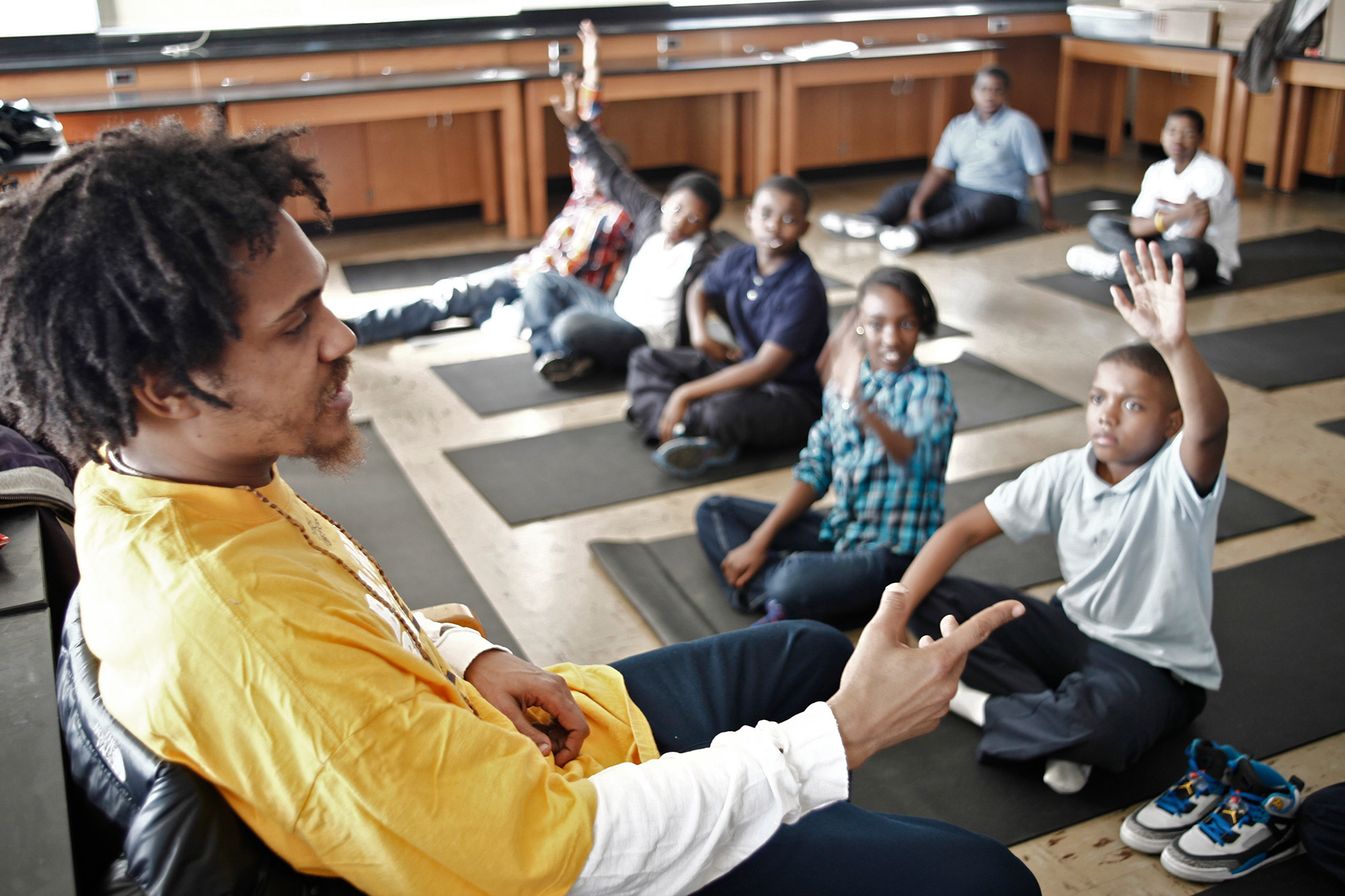 man teaching young people on yoga mats