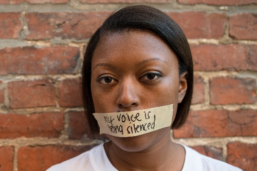 "woman with taped mouth that reads ""my voice is being silenced"""