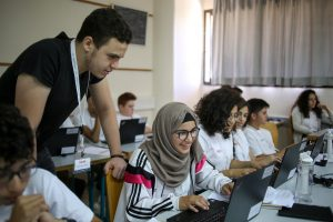 teacher assisting students working on laptops