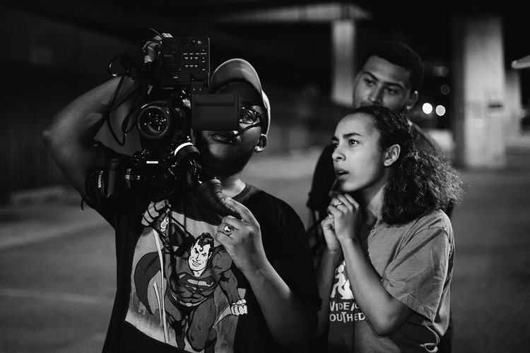 three young people filming